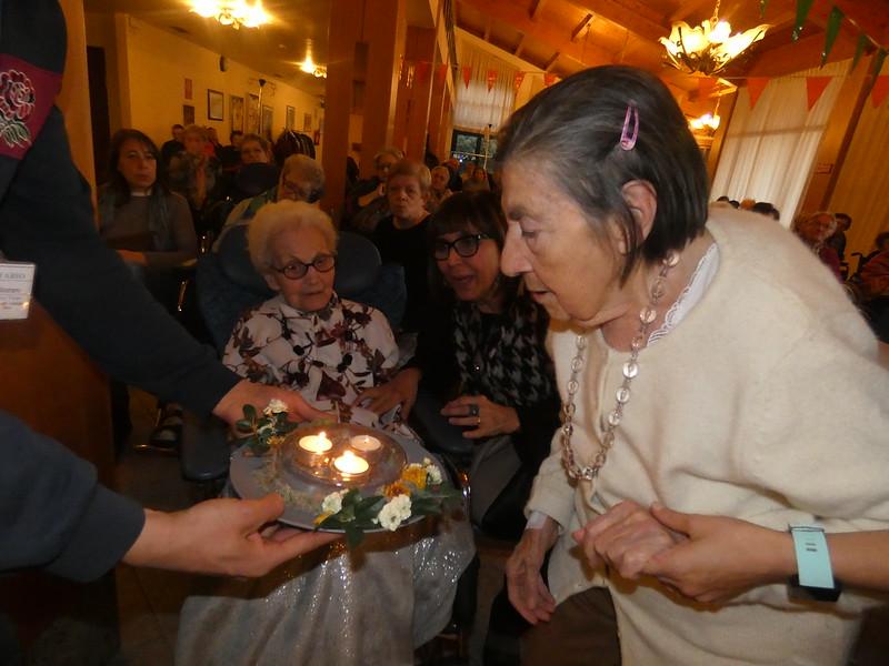 Una delle festeggiate che soffia sulle candeline durante la festa